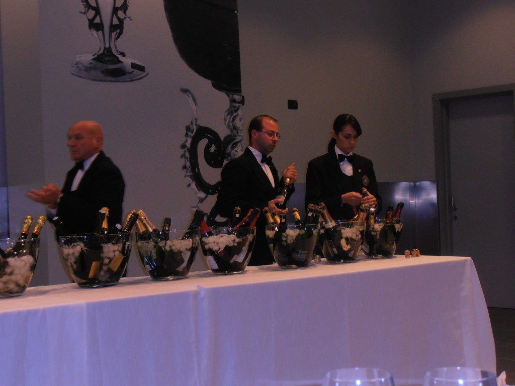 Sommeliers opening bottles at the comparative sparkling wine tasting