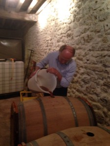 Hervé Jestin filling up barrels and informing the must